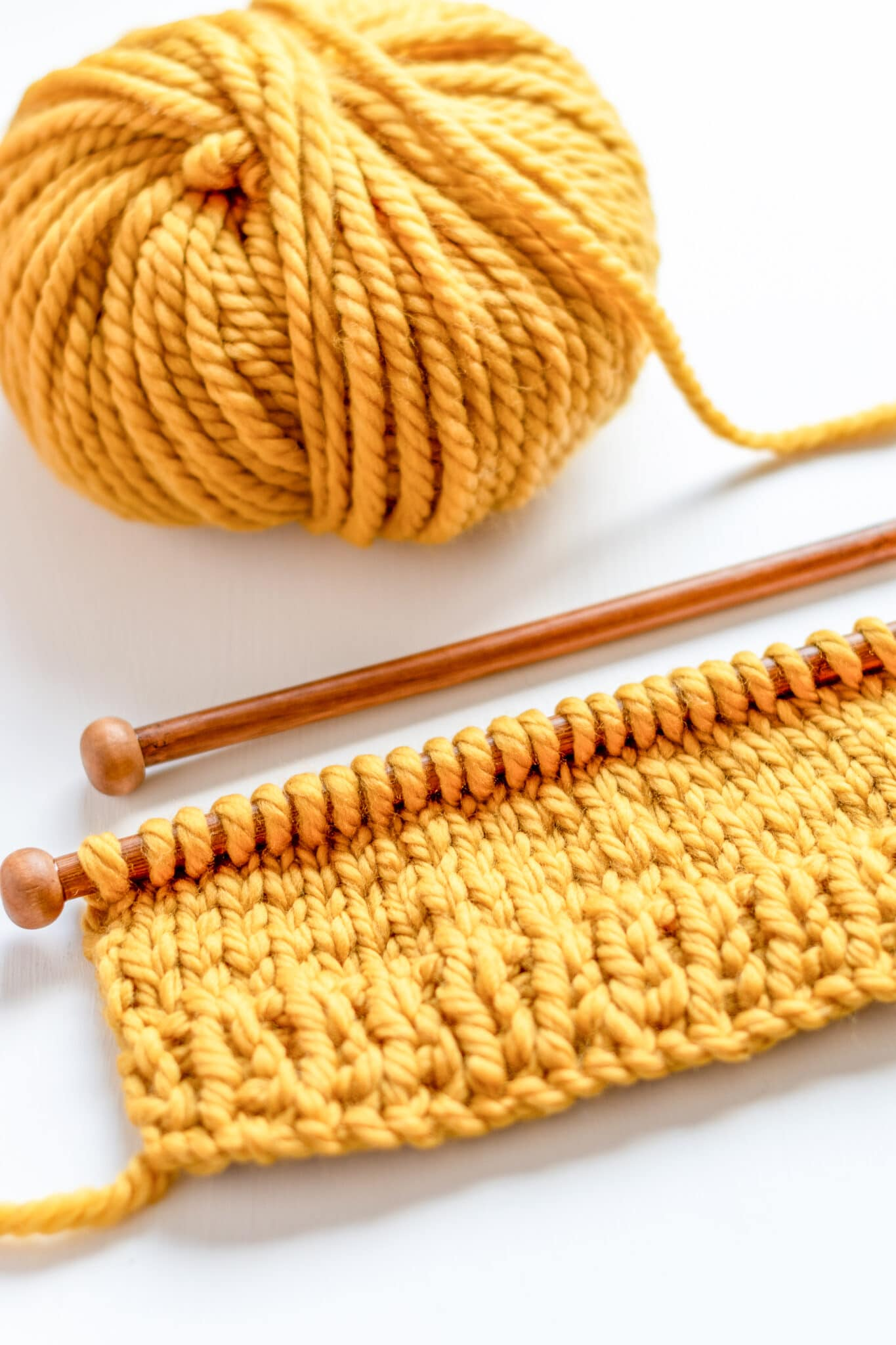 A bright yellow ball of chunky wool being knit on a wooden knitting needle.