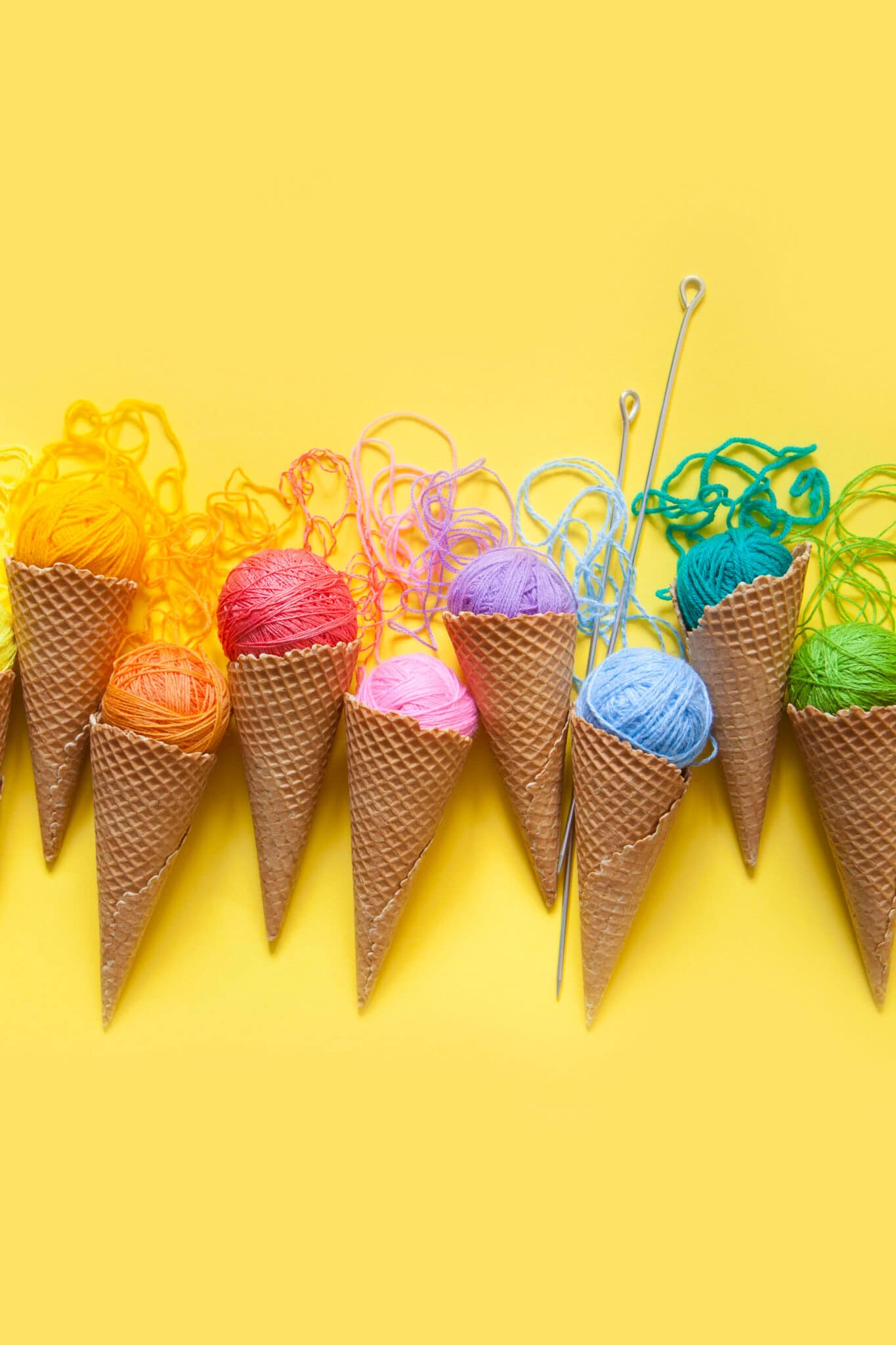 Balls of yarn lie in a waffle cone for ice cream. Coloured wool against a bright yellow background.
