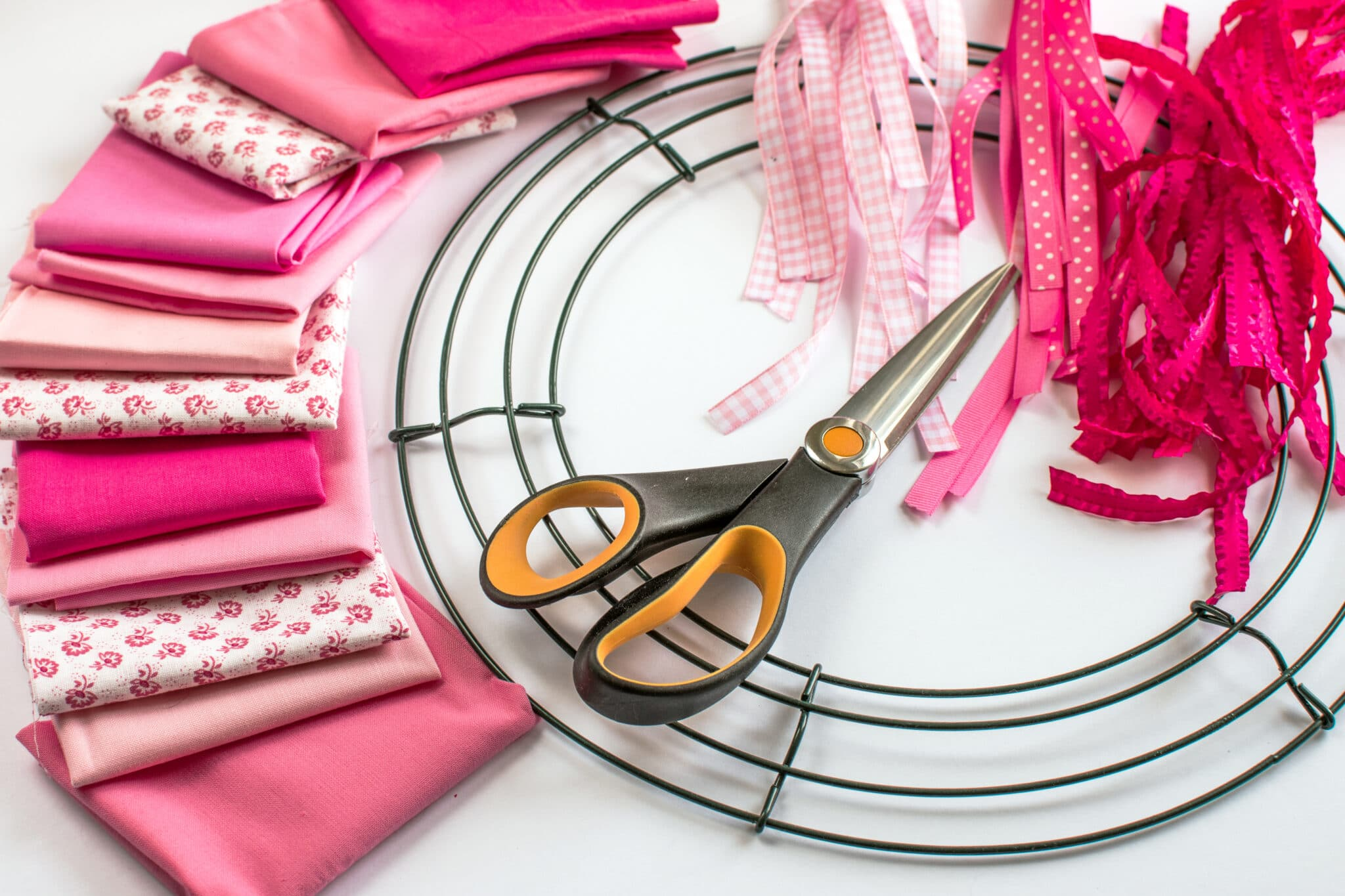 Wreath making supplies on a bright white table top.  Fiskars scissors, ribbon, fabric quarters and a wire wreath form.