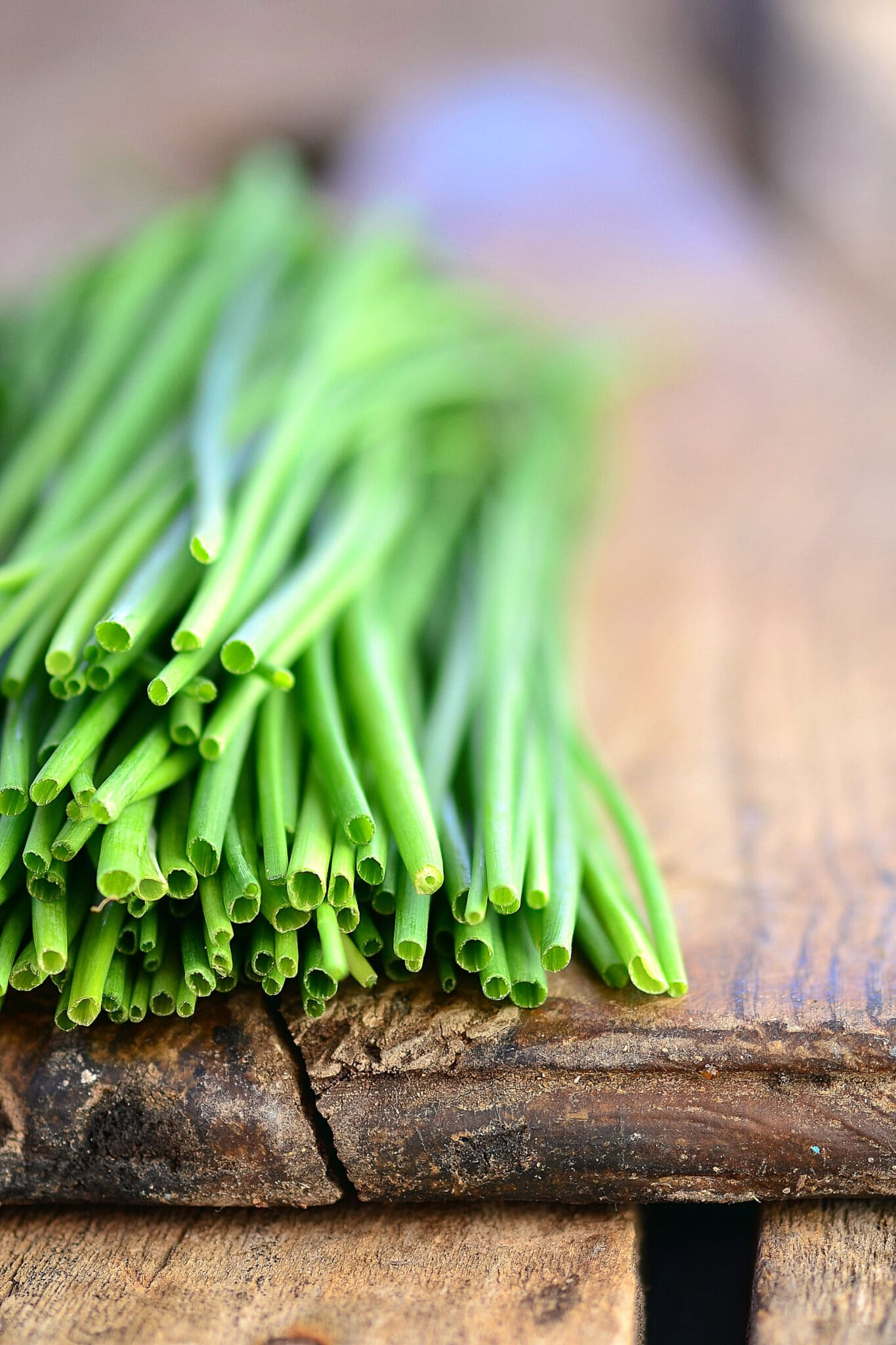 A freshly cut bunch of chives resting a very rustic and old wood cutting board.