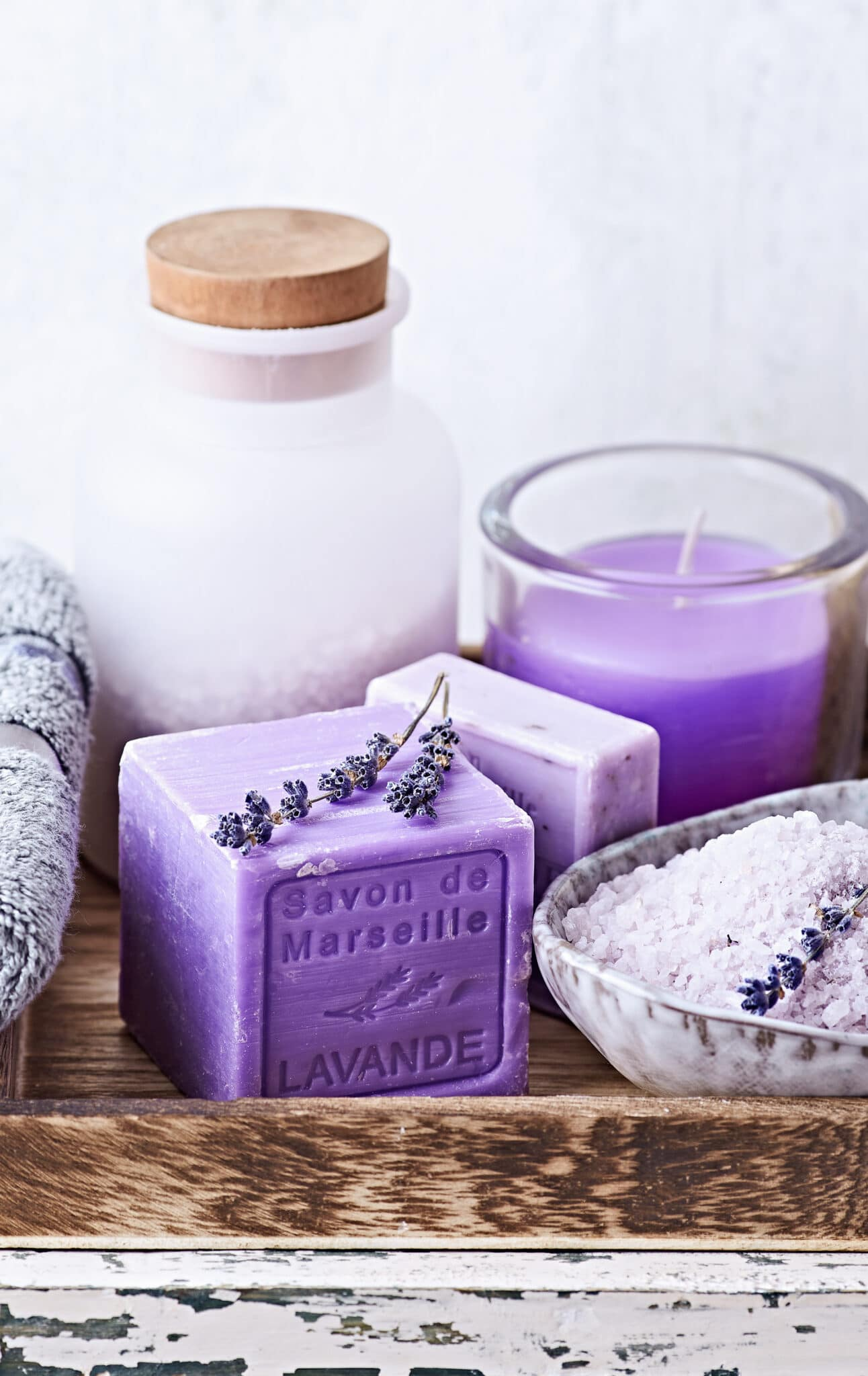 Lavender soap and bath salts with a lavender candle on a rustic wooden tray.