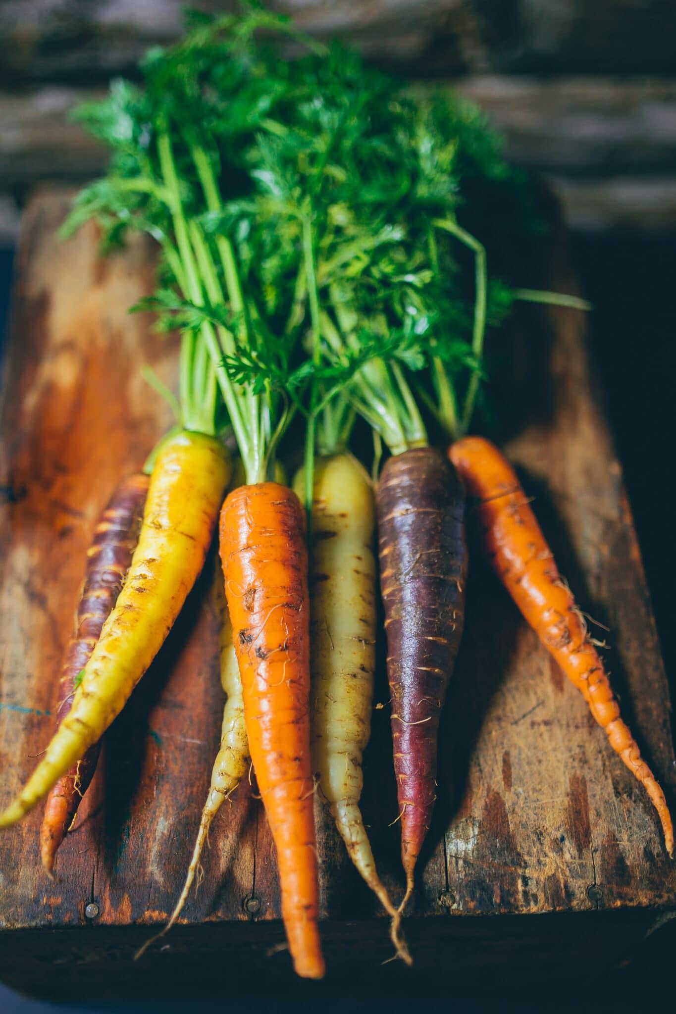Garden fresh rainbow carrots on a rustic cutting board.