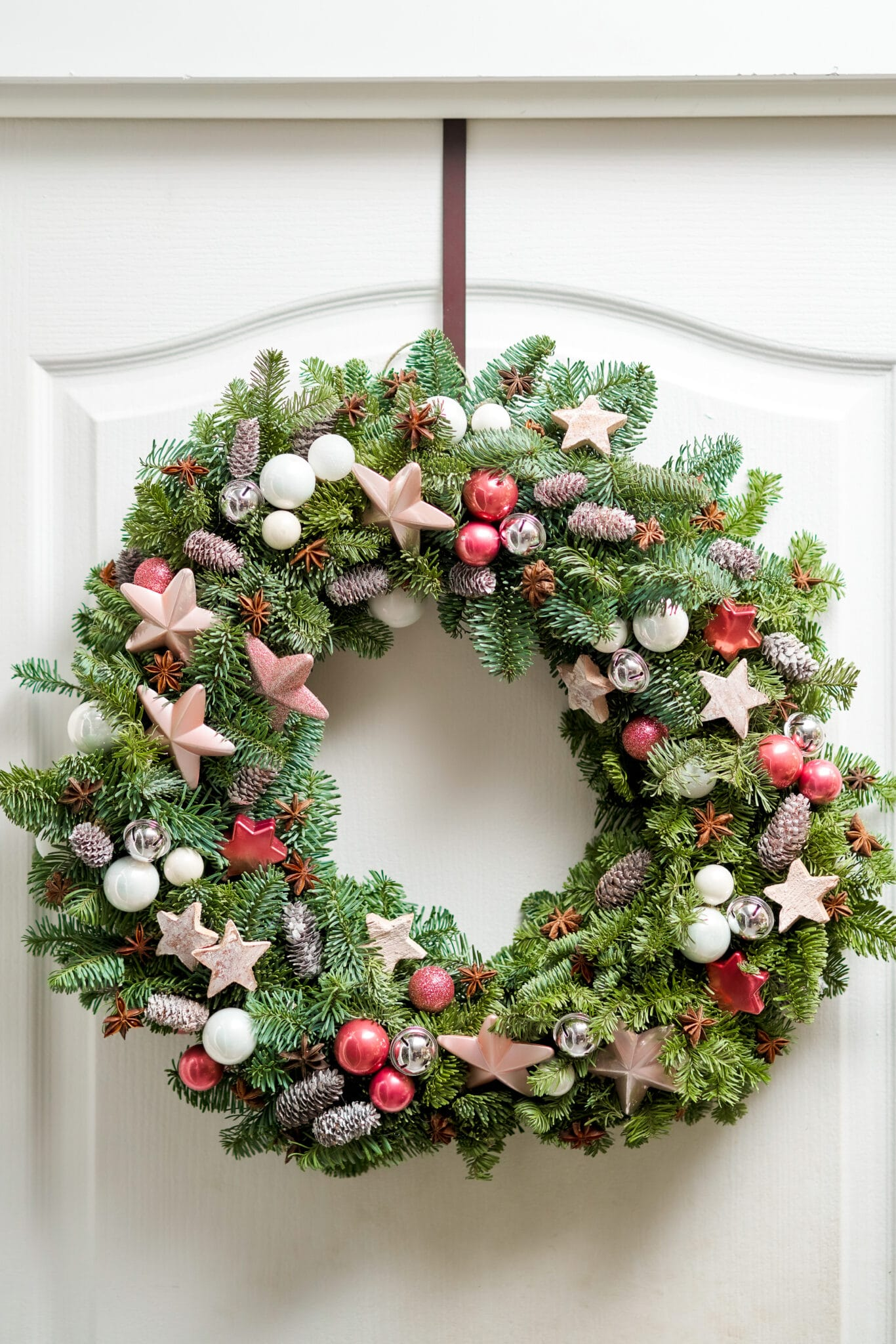 Beautiful Christmas wreath of fresh spruce on the white door. Entrance to the house.