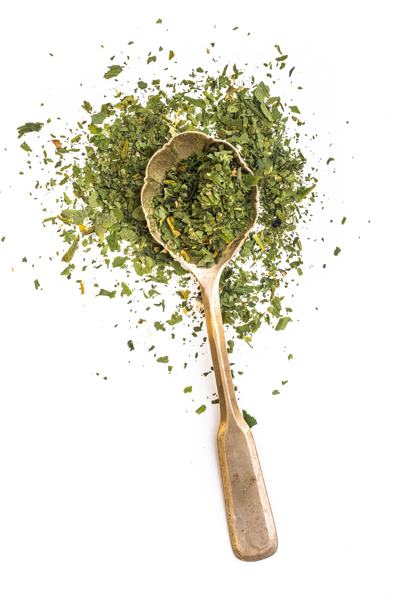 dried parsley in a spoon isolated on a white background.