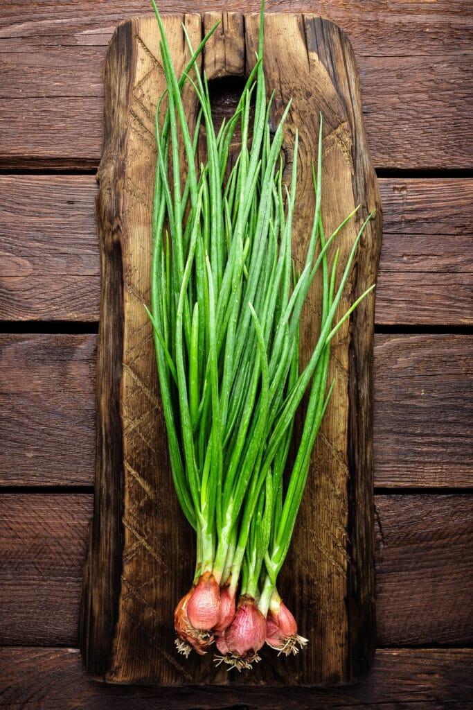 fresh green onions on a rustic cutting board.
